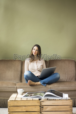 smiling young woman sitting on couch