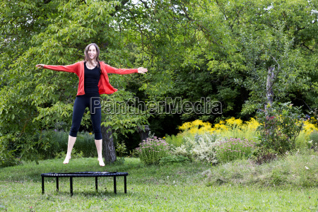 laughing woman jumping on trampoline in