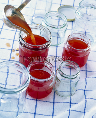 pouring plum jam into jars