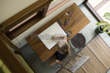little girl sitting at table drawing