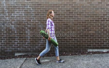 young, woman, walking, down, sidewalk, carrying - 23575714