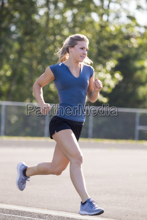 young woman running on track eugene