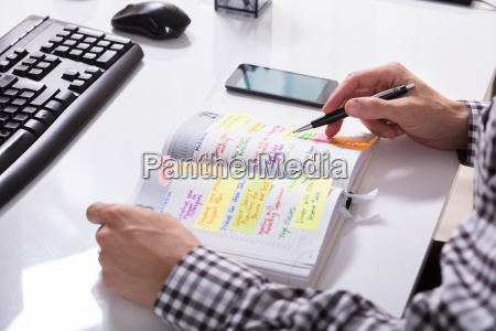 businessperson, with, mobile, phone, writing, schedule - 23578504