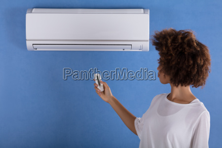 woman, adjusting, air, conditioner, with, remote - 23578548
