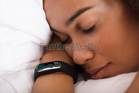 woman, sleeping, on, bed, with, smartwatch - 23578448