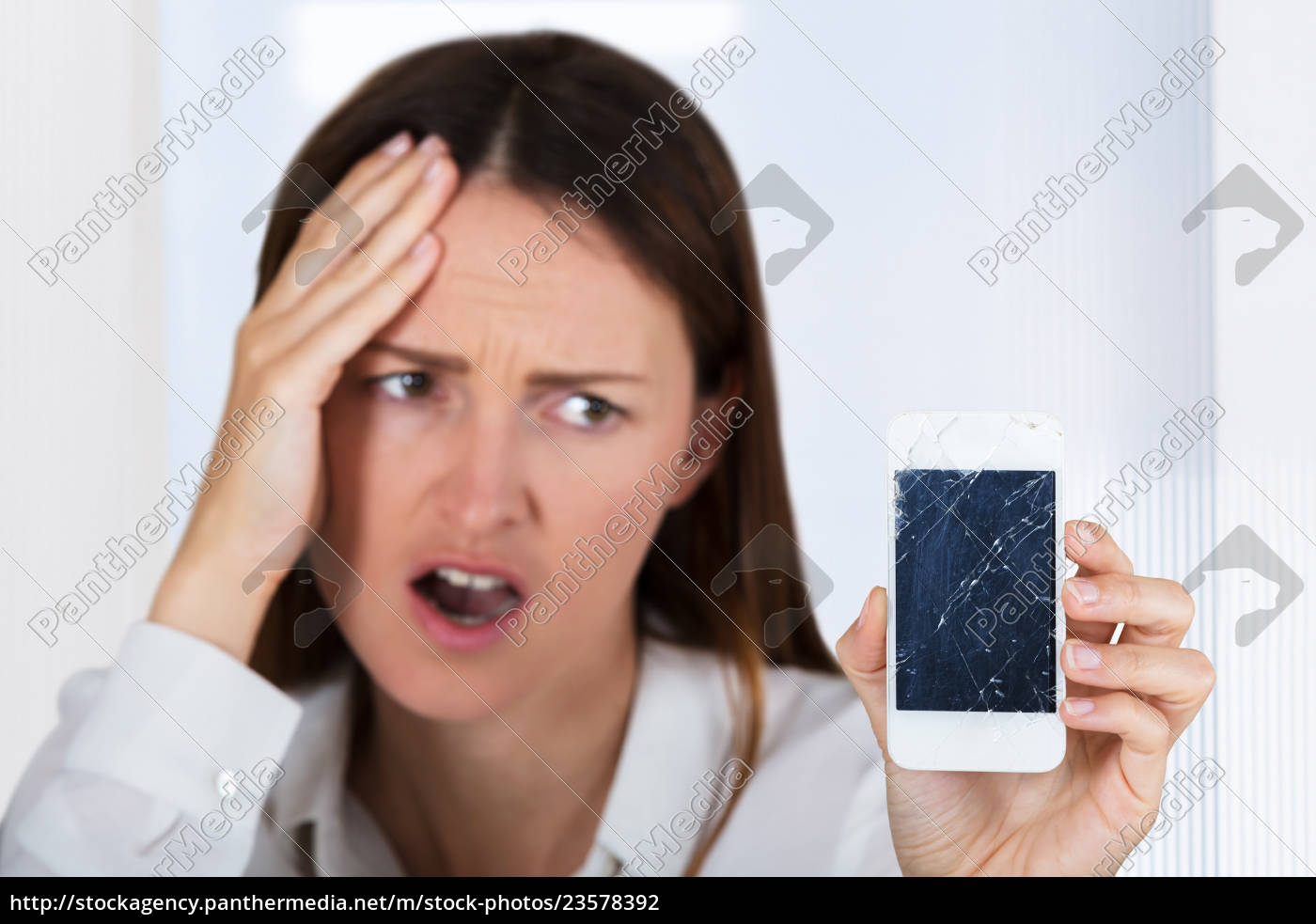 worried, woman, holding, smartphone, with, cracked - 23578392