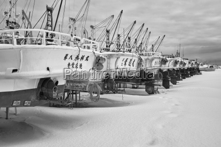 row of fishing boats on dry
