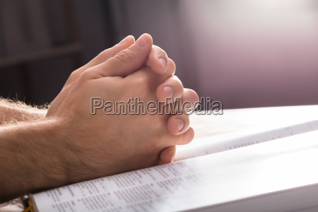 praying hands over the bible