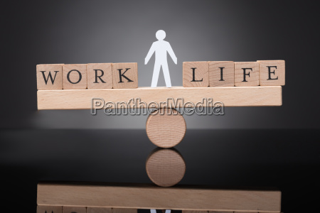 human figure balancing between work and