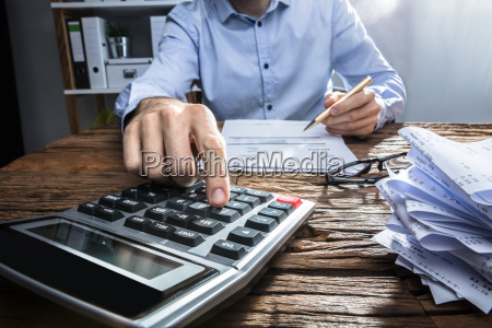 businessperson, calculating, invoice, with, calculator - 23584100
