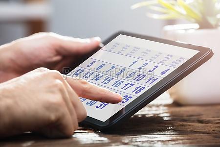 businessperson, using, calendar, on, digital, tablet - 23584152