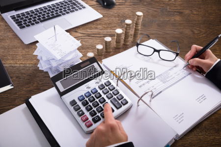 close-up, of, a, businessperson, calculating, invoice - 23584684