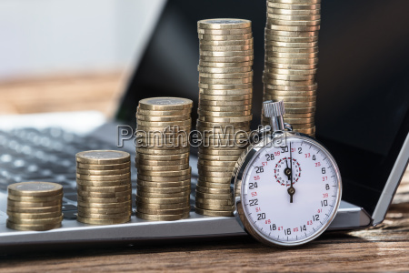 stopwatch, with, stacked, coins, on, laptop - 23584148