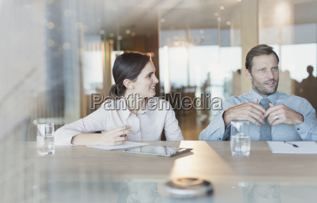 businesswoman listening to businessman in conference