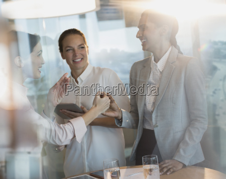 businesswomen laughing handshaking in office meeting