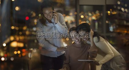 happy businesswomen celebrating working late in