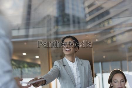 smiling businesswoman handing paperwork to colleague