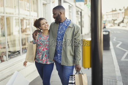 affectionate young couple with shopping bags