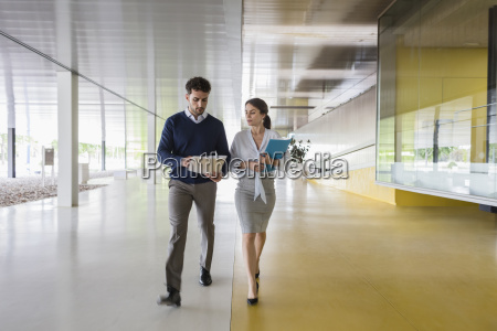 businessman and businesswoman walking and discussing