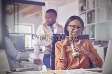 portrait smiling confident businesswoman drinking green