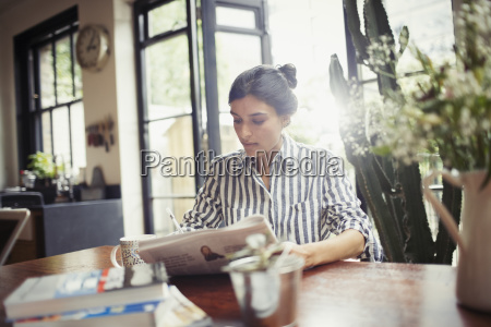 young woman with newspaper at dining