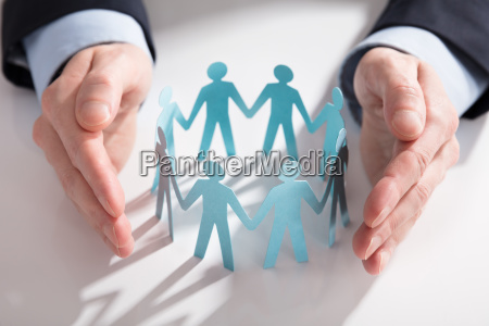 businesspersons hand protecting paper cut out