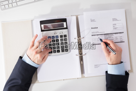businessperson, checking, invoice, with, calculator - 23595582