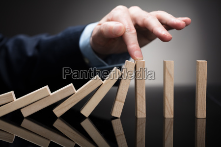 businessperson, stopping, wooden, blocks, from, falling - 23595604