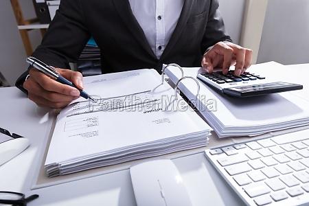 close-up, of, a, businessperson, calculating, bill - 23595212