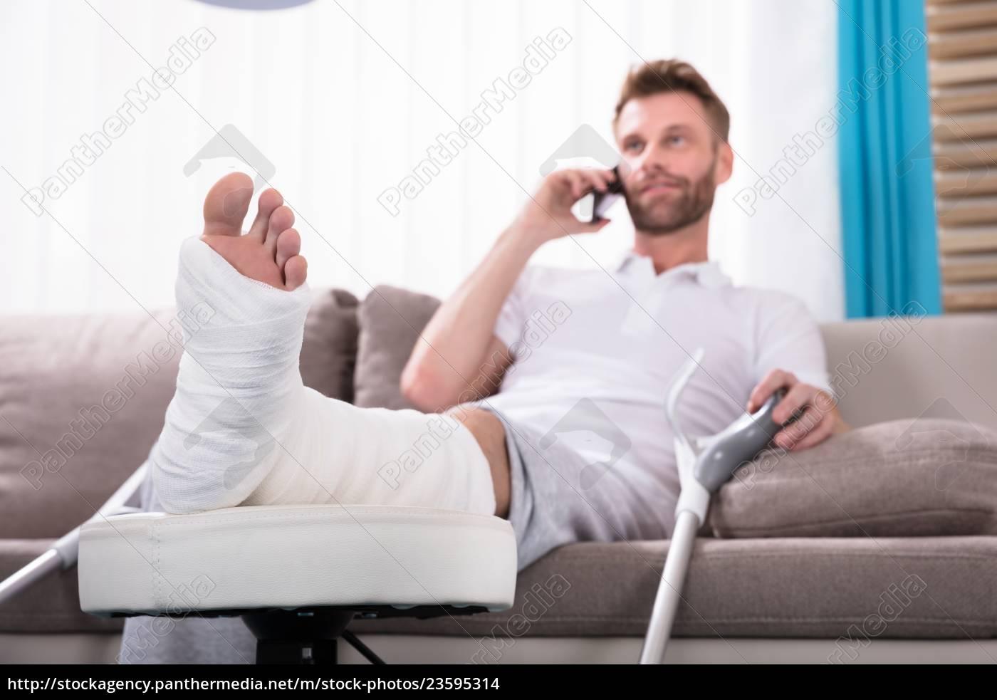 happy, young, man, with, broken, leg - 23595314