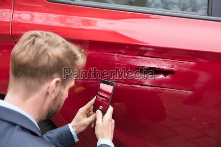 person, taking, picture, of, damaged, car - 23595616