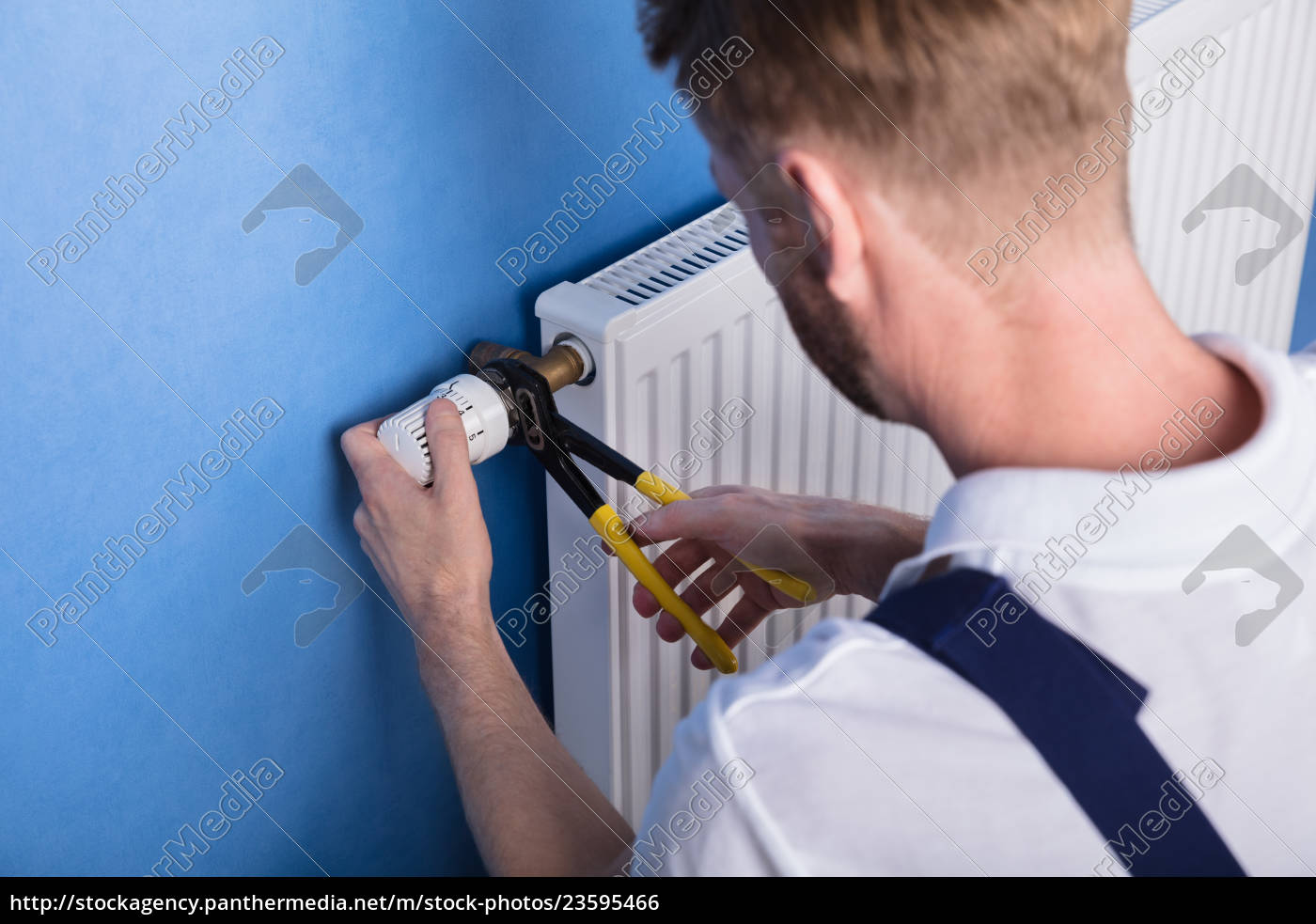 repairman, fixing, radiator, with, wrench - 23595466
