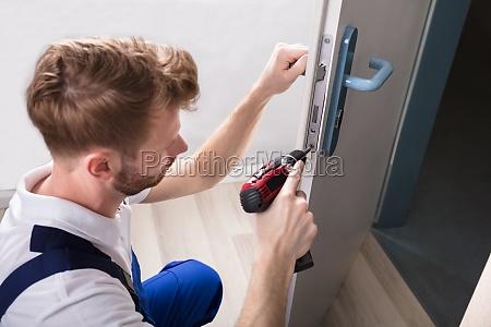 young, carpenter, install, door, lock - 23595476