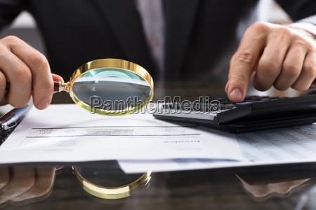 businessperson, calculating, bill, with, magnifying, glass - 23596962