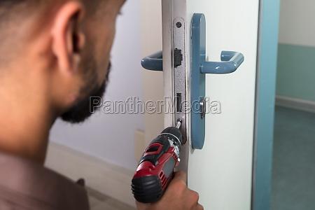 carpenter installing door lock with wireless