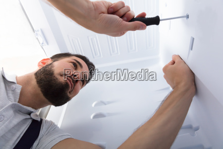 electrician fixing refrigerator in kitchen