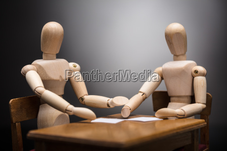 two wooden dummy figures making business