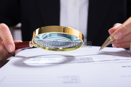 auditor, inspecting, financial, documents, at, desk - 23597004