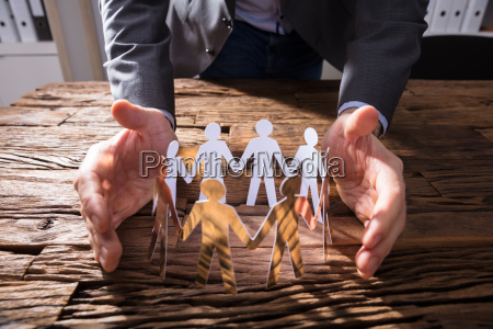 businessperson, protecting, paper, cut, out, figures - 23597848