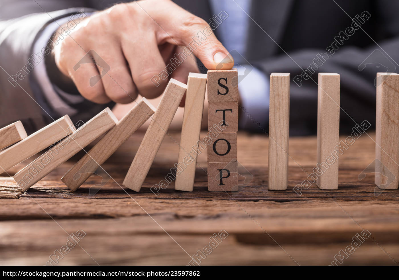 businessperson's, finger, stopping, falling, dominos - 23597862