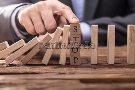 businessperson's, finger, stopping, falling, dominos - 23597862