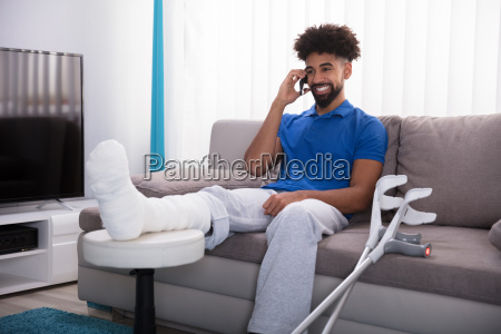happy, young, man, with, broken, leg - 23597238