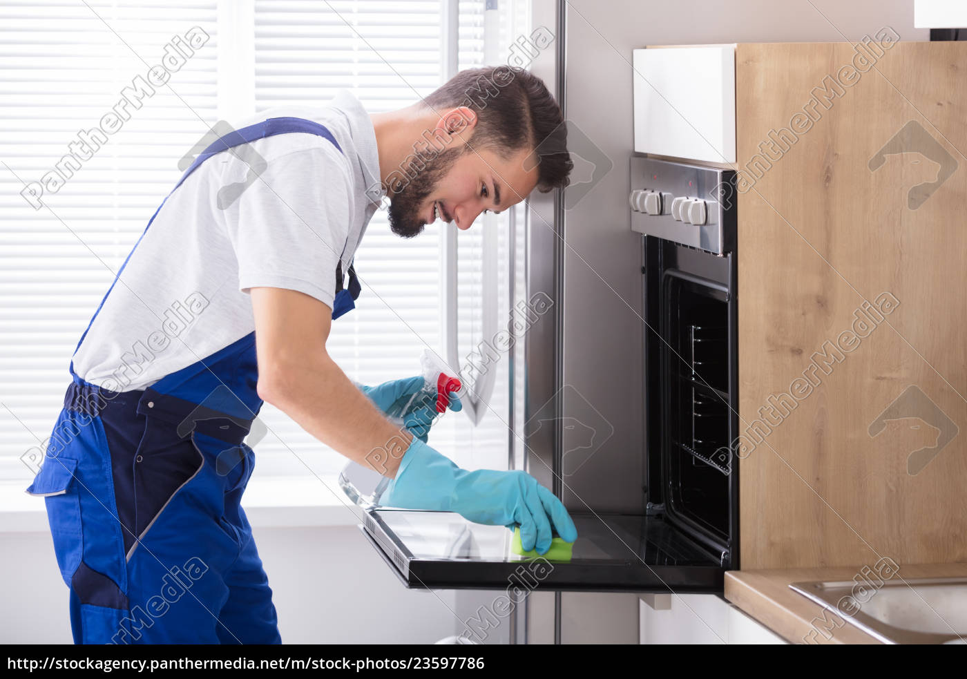 janitor, cleaning, oven, in, kitchen - 23597786