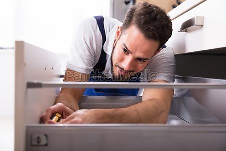 male, carpenter, installing, drawer - 23597820