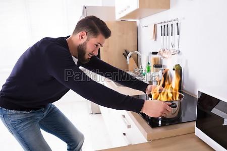 man, holding, utensil, on, fire - 23597794