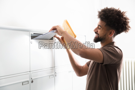 man, putting, letters, in, mailbox - 23597140