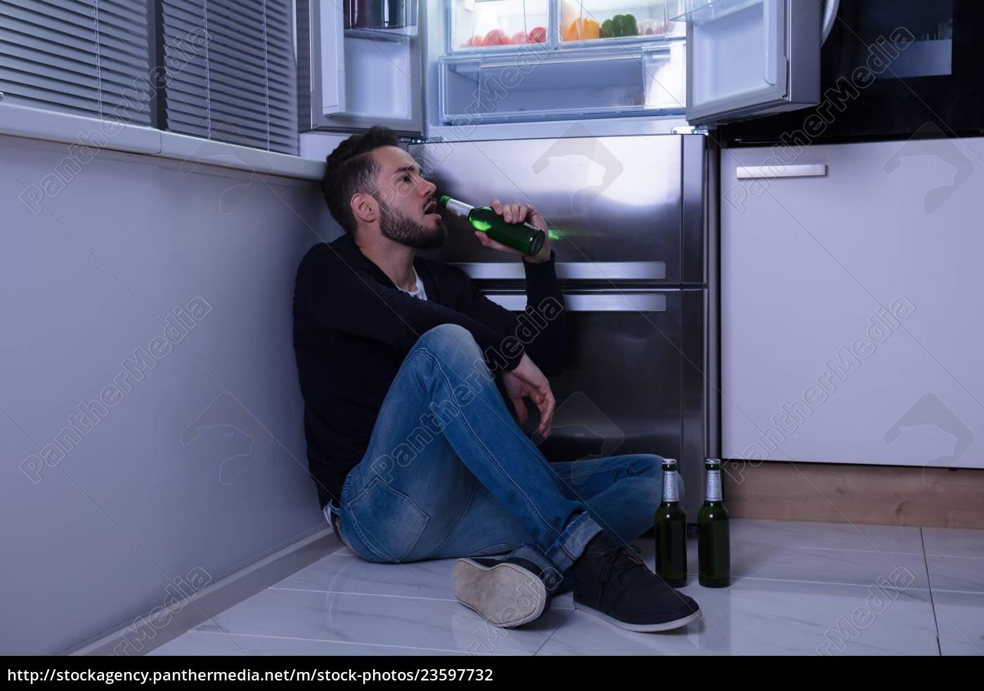 man, sitting, on, floor, drinking, beer - 23597732