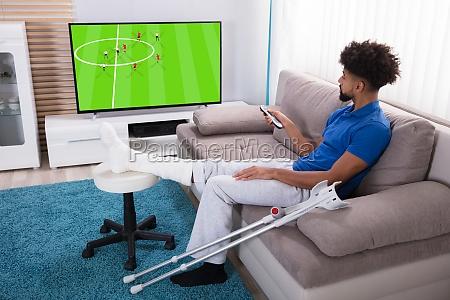 man, with, broken, leg, watching, football - 23597176