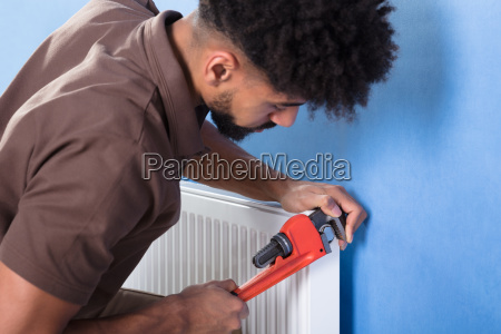 plumber, fixing, radiator, with, wrench - 23597156