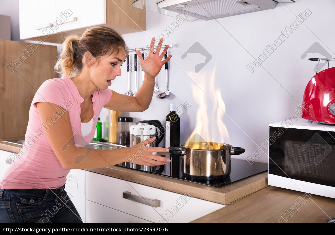 shocked, young, woman, looking, at, cooking - 23597076